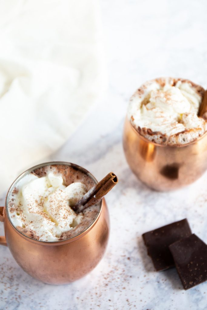 Two copper mugs filled with Mexican hot chocolate.