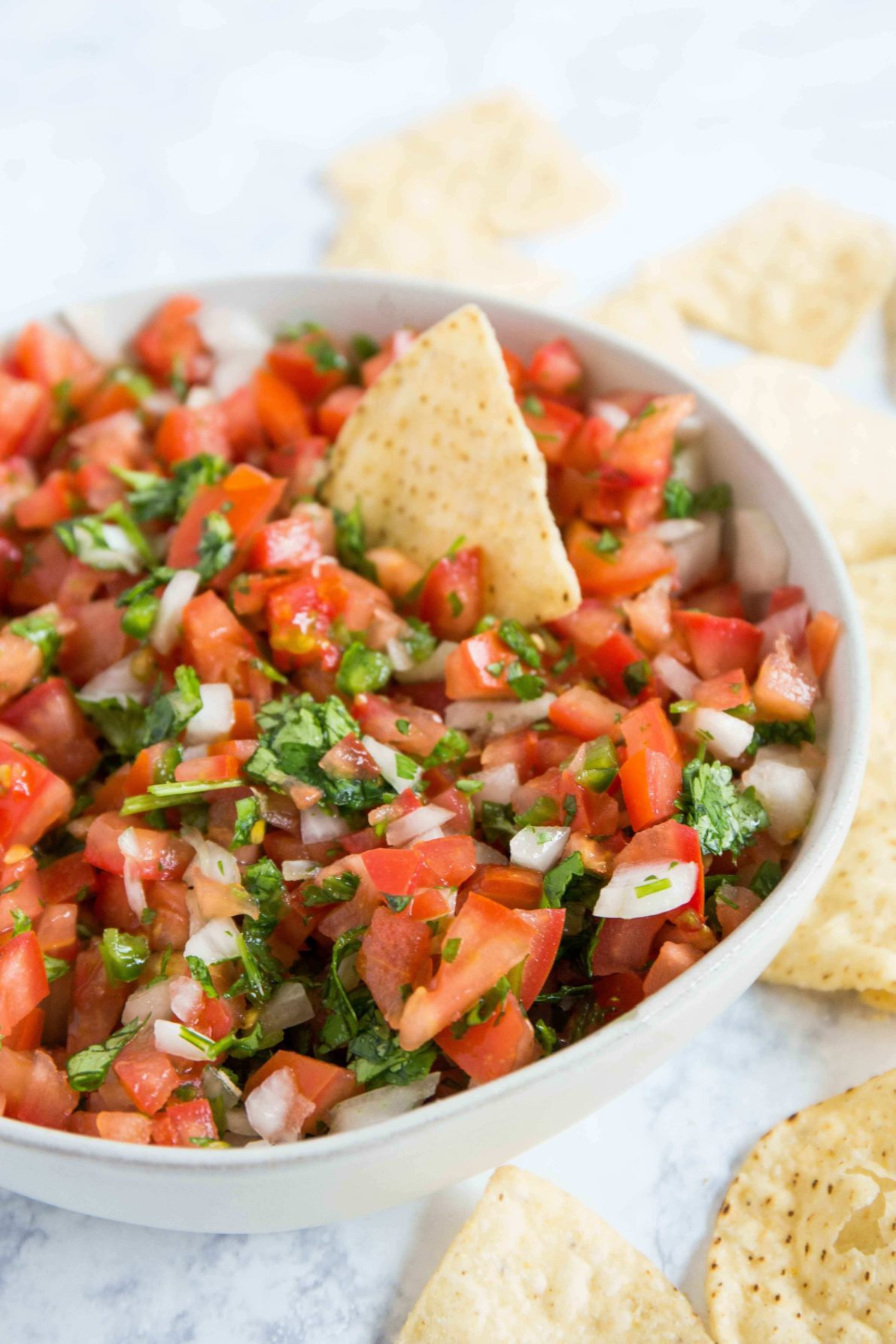 Pico de gallo in a bowl with chips around it.