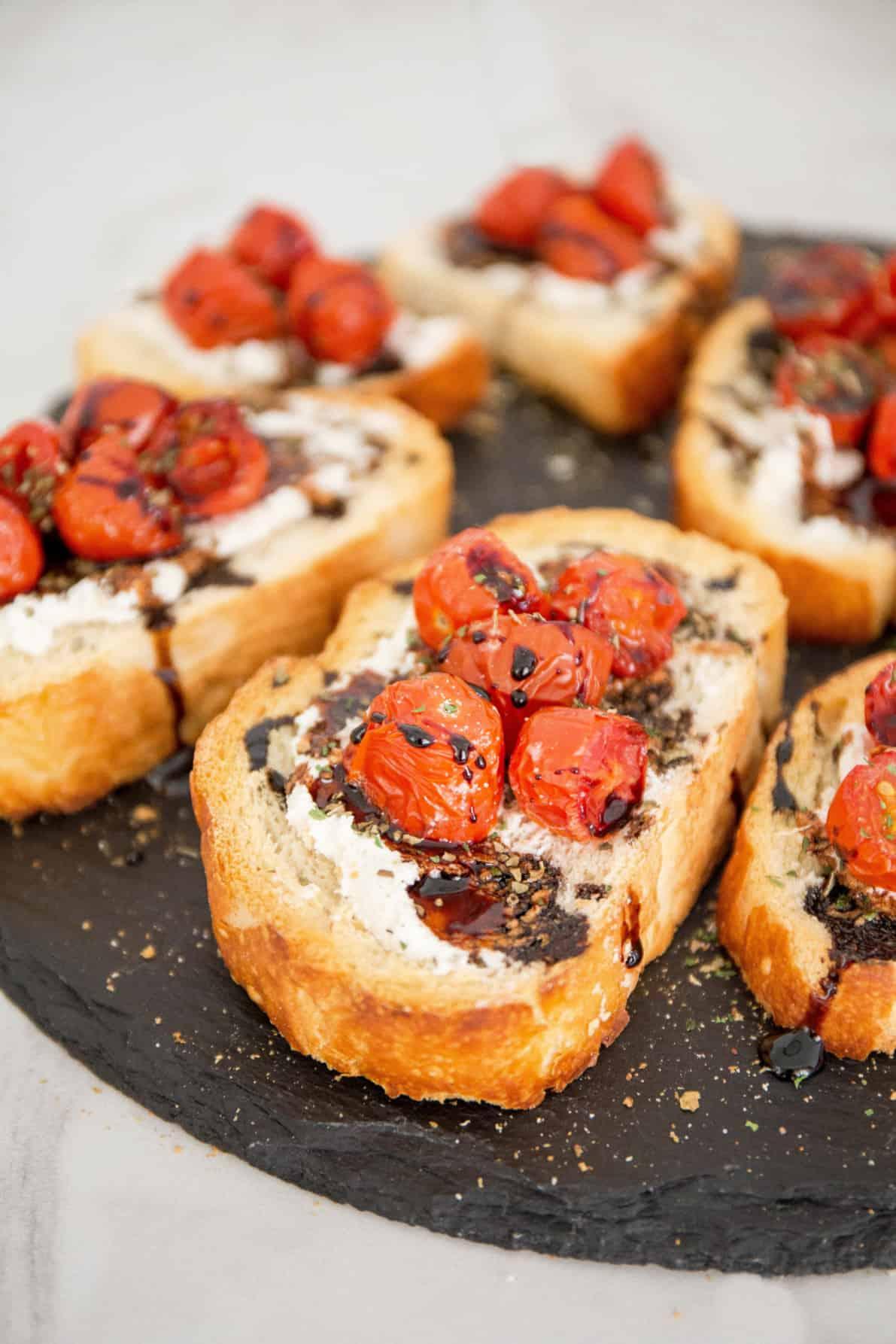 Roasted Tomato Bruschetta on a slate surface.