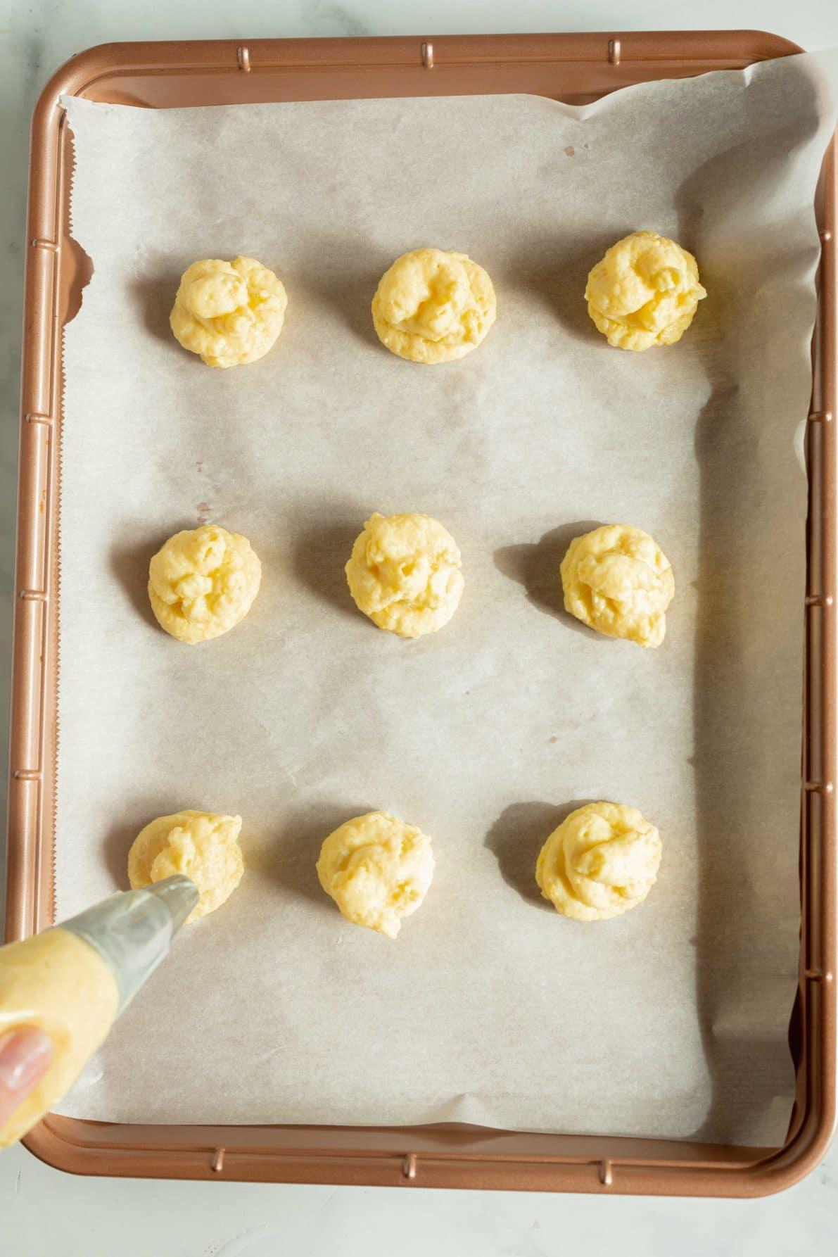 Dollops of custard mochi on a cookie sheet.